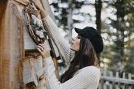 Young woman decorating wooden house with Christmas decoration - OCAF00106