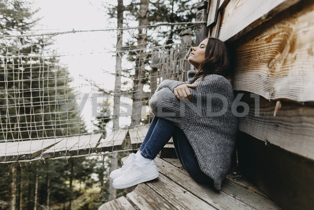 Young woman sitting at a wooden house in the nature relaxing - OCAF00112