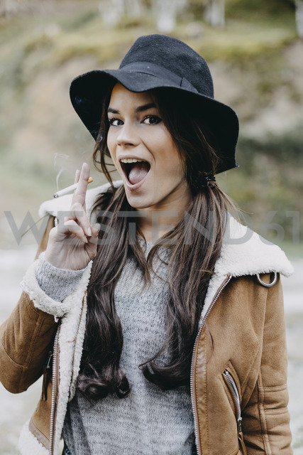 Portrait of happy young woman wearing flappy hat and smoking a cigarette in the nature - OCAF00115