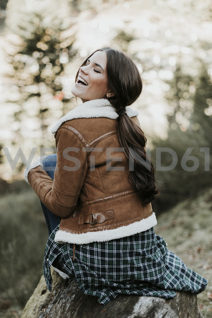 Happy young woman sitting on a log in the nature - OCAF00118