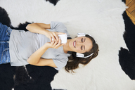 Smiling young woman lying on fur with headphones and cell phone - BSZF00153