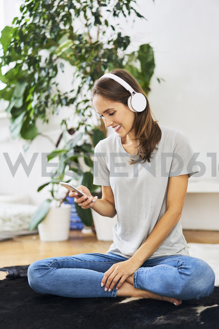 Smiling young woman sitting on the floor with headphones and cell phone - BSZF00156