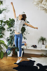 Exuberant young woman jumping in a room - BSZF00162