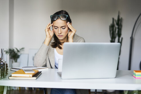 Young woman at home with laptop on desk touching her temples - BSZF00168