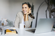 Happy young woman at home with laptop on desk - BSZF00171