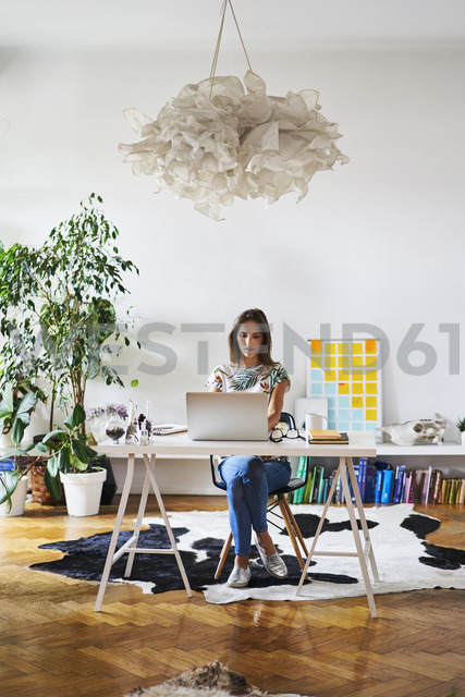 Young woman at home using laptop on desk - BSZF00192
