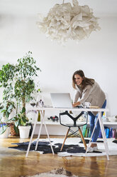 Smiling young woman at home using laptop on desk - BSZF00195