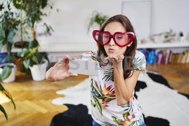 Young woman in heart-shaped glasses taking selfie - BSZF00198