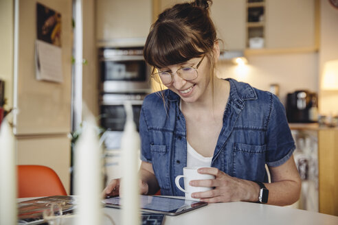 Smiling woman sitting with cup of coffee at table in the kitchen using tablet - MFF04372