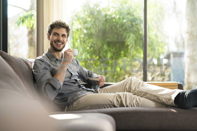 Laughing man relaxing on couch at home drinking coffee - SBOF01259 - Steve Brookland/Westend61