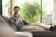 Laughing man relaxing on couch at home drinking coffee - SBOF01259