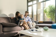Smiling parents and son sitting on sofa at home - SBOF01265