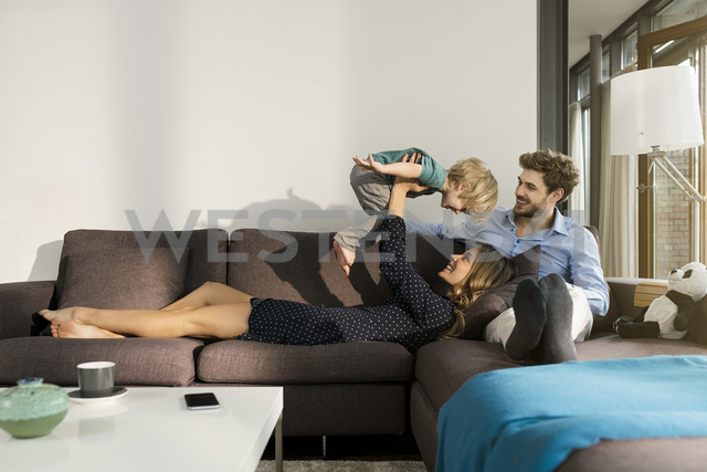 Happy parents playing with son on sofa at home - SBOF01268
