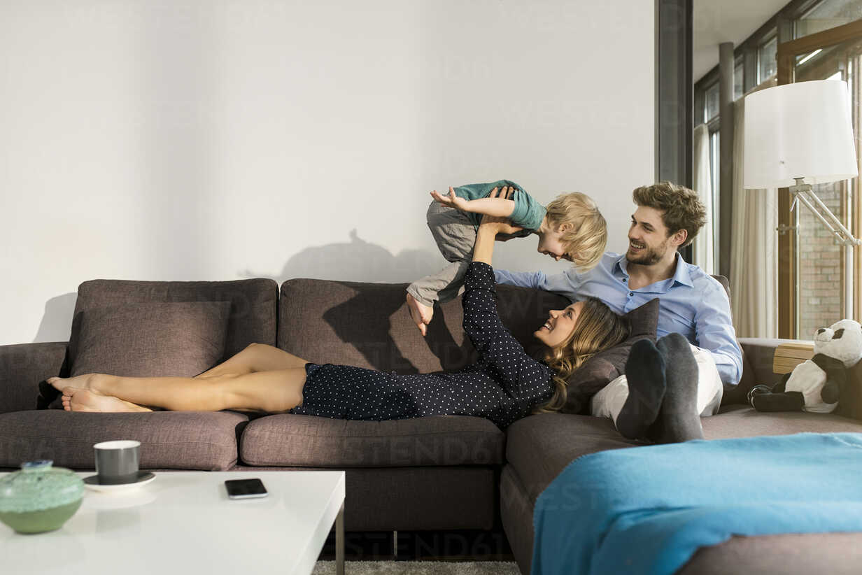 Happy parents playing with son on sofa at home - SBOF01268 - Steve Brookland/Westend61