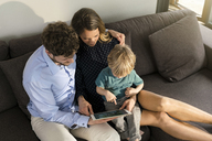 Parents and son sitting on sofa holding tablet at home - SBOF01271