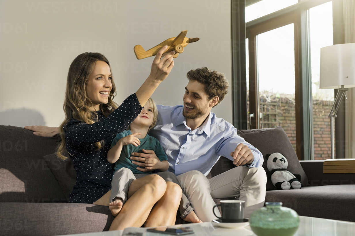 Happy parents and son playing with wooden toy plane on sofa at home - SBOF01274 - Steve Brookland/Westend61