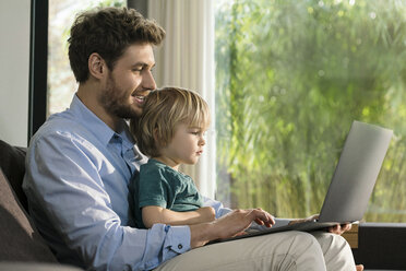 Father and son looking at laptop on couch at home - SBOF01277