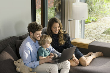 Smiling parents and son sitting on sofa using laptop at home - SBOF01280