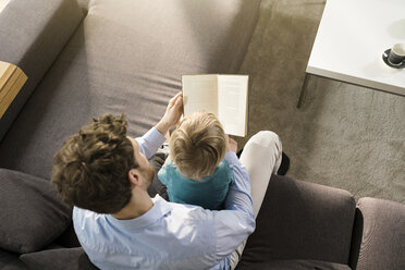 Father and son reading book on couch at home - SBOF01283