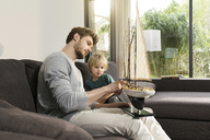 Father and son looking at toy model ship on couch at home - SBOF01286