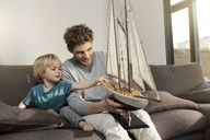 Father and son looking at toy model ship on couch at home - SBOF01289