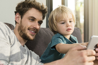 Father and son looking at smartphone on couch at home - SBOF01292
