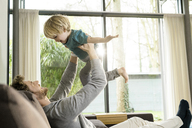 Happy father playing with son on sofa at home - SBOF01295