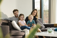 Portrait of happy family sitting on sofa at home - SBOF01301