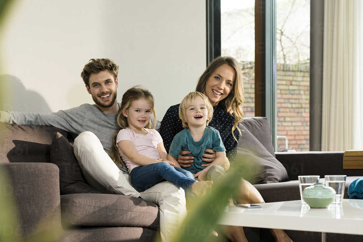 Portrait of happy family sitting on sofa at home - SBOF01301 - Steve Brookland/Westend61