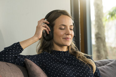 Portrait of smiling woman with headphones relaxing on couch at home - SBOF01307