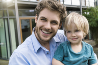 Portrait of smiling father with son in front of their home - SBOF01310