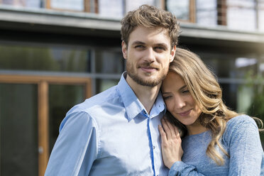 Portrait of smiling affectionate couple in front of their home - SBOF01316