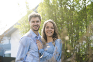 Portrait of smiling couple in garden in front of bamboo plants - SBOF01319