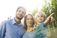 Smiling family in front of bamboo plants with son pointing his finger - SBOF01322
