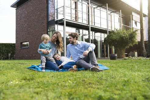 Happy family on blanket in garden in front of their home - SBOF01325