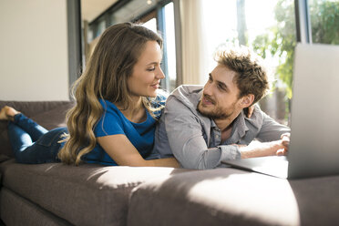 Smiling couple with laptop lying on sofa at home - SBOF01328