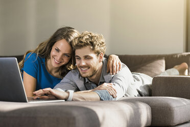 Smiling couple using laptop lying on sofa at home - SBOF01331