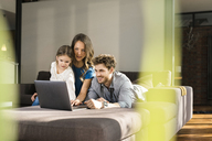 Family using laptop on sofa at home - SBOF01334