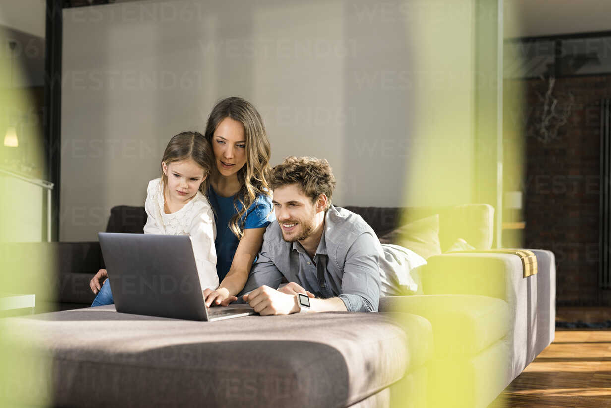 Family using laptop on sofa at home - SBOF01334 - Steve Brookland/Westend61