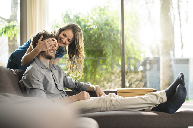 Smiling woman covering her boyfriend's eyes on sofa at home - SBOF01337 - Steve Brookland/Westend61
