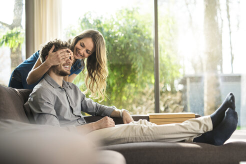 Smiling woman covering her boyfriend's eyes on sofa at home - SBOF01337