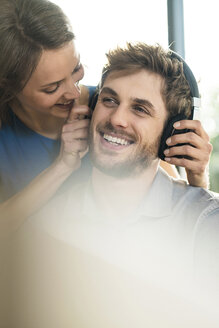 Smiling woman putting on headphones on boyfriend - SBOF01340