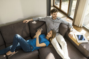 Smiling couple with tablet and smartphone relaxing on sofa at home - SBOF01343