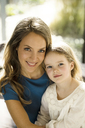 Portrait of smiling mother with daughter in front of window - SBOF01349