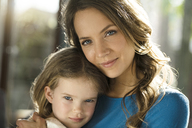 Portrait of smiling mother with daughter in front of window - SBOF01352