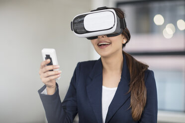 Smiling businesswoman wearing VR glasses in office - ZEF14912