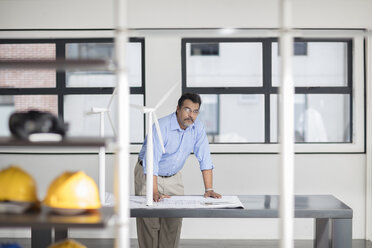 Man with blueprint and wind turbine models in office - ZEF14915