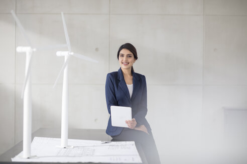 Portrait of smiling young woman with blueprint, wind turbine models and tablet in office - ZEF14918