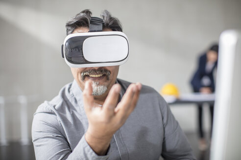 Man wearing VR glasses in office - ZEF14924
