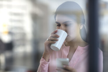 Portrait of young woman with cell phone and coffee in the office - ZEF14930